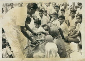 Priest Junesh Raika serves communion to an RLDS congregation in Odisha, India, ca. 1968; image courtesy of Community of Christ Archives.
